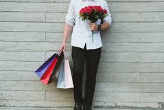 Man holding colorful shopping bag & red rose bouquet outdoors. s. Young man holding colorful shopping bag & red rose bouquet outdoors. shopaholic male standing Royalty Free Stock Photos