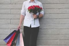 Man holding colorful shopping bag & red rose bouquet outdoors. s. Young man holding colorful shopping bag & red rose bouquet outdoors. shopaholic male standing Stock Photos