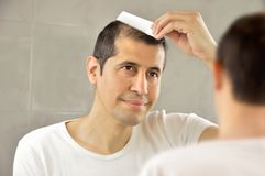 Man looking himself fresh at the mirror stock photography