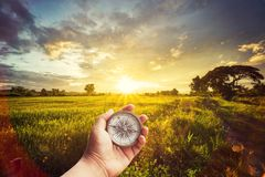 A man holding compass on hand at field and sunset for navigation. Guide Stock Photo