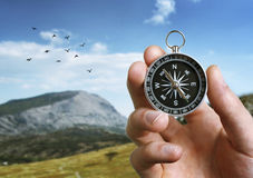 Man holding a compass over a landscape view Stock Photos