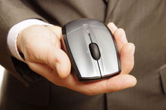 Man holding computer mouse. Office worker holding wireless computer mouse in hand wearing grey suit Royalty Free Stock Photos