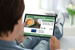Man holding computer tablet with app delivery food on screen royalty free stock photos