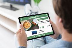 Man holding computer tablet with app delivery food on screen royalty free stock image