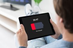 Man holding computer tablet with low charged battery on screen Stock Image