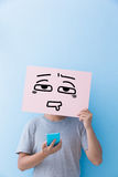 Man holding confused expression billboard. And take phone isolated on blue background royalty free stock photos