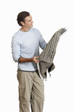 Man holding and considering piece of fabric, cut out Stock Photography
