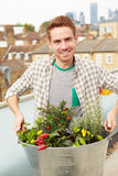 Man Holding Container Of Plants On Rooftop Garden Royalty Free Stock Photography