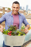 Man Holding Container Of Plants On Rooftop Garden Royalty Free Stock Image