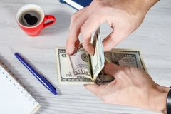 Man is holding and counting dollar bills. Man ise holding and counting dollar bills. Cup of coffee, notebook and pen are on the background. Top view stock photography