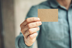 Man holding craft business card on concrete wall Royalty Free Stock Image