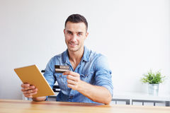 Man holding credit card and digital tablet royalty free stock image