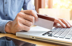 Man holding credit card in hand and entering security code using Stock Photography