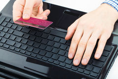 Man holding a credit card next to computer keyboard and trying to do online payment Royalty Free Stock Images