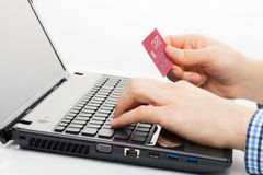 Man holding a credit card next to computer keyboard and trying to do online shopping. Man holding a credit card next to keyboard and trying to do online shopping Royalty Free Stock Photography