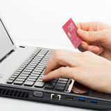 Man holding a credit card next to computer keyboard and trying to do online shopping - close up studio shot Royalty Free Stock Photo