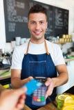 Man holding credit card reader at cafe Royalty Free Stock Photo