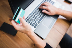 Man holding a credit card and typing Royalty Free Stock Images