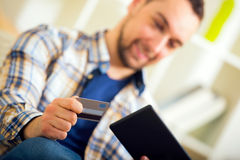 Man holding credit card and using digital tablet for online shopping Stock Images