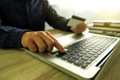 Man holding credit card and using laptop for payment shopping on royalty free stock photography