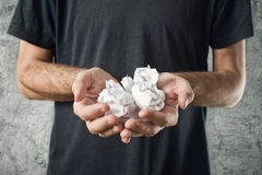 Man holding crumpled pieces of paper Royalty Free Stock Image