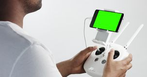Man holding a cuadrocopter control remote and using a smartphone with green screen. Studio product footage stock video footage