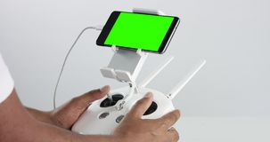 Man holding a cuadrocopter control remote and using a smartphone with green screen. Studio product footage stock footage