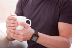 Man holding a cup in both hands. I need some coffee. Close up of hands of a man holding a cup with both hands and wearing smartwatch Stock Photography