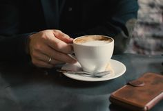 Man holding a cup of cappuccino. royalty free stock photo