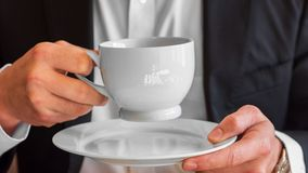 Man holding a cup of coffee with cream and small white plate, dressed in white dress shirt and black suit and wearing a watch stock photo