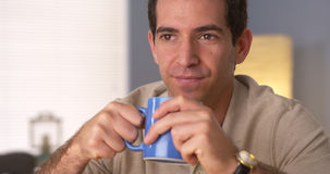 Man holding a cup of coffee while looking away Stock Images
