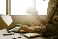 A man holding a cup of coffee and working on laptop in offic. A man holding a cup of coffee and working on laptop on his office desk,toned with sunlight Royalty Free Stock Photography