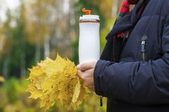Man holding cup with drink and autumn leaves Stock Images