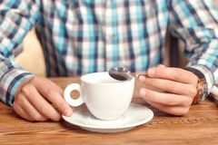 Man holding cup and tea spoon. Coffee time. Close up portrait of young man having cup and tea spoon in cafe Stock Images