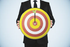 Man holding a dart board with a direct hit on target Stock Photos