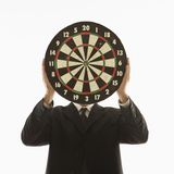 Man holding dartboard in front of face. Caucasian man wearing suit and holding dartboard in front of face Royalty Free Stock Photography