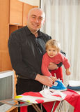 Man holding  daughter  and ironing Royalty Free Stock Images