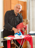 Man holding  daughter and ironing Stock Image