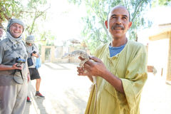 Man holding desert monitor in Tozeur Zoo Stock Images