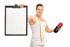 Man holding a diet pill and a clipboard Stock Photography