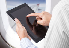 Man holding digital tablet at airplane Royalty Free Stock Photo