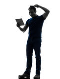 Man holding digital tablet  brushing hair silhouette Royalty Free Stock Photos