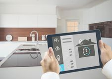 Man holding a digital tablet with home security concept. With kitchen in background stock photography