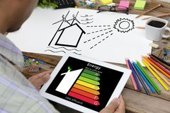 Man holding digital tablet and looking at house efficiency rating. Detail of house efficiency rating on digital tablet screen. Concept of ecological and bio stock photo