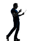 Man holding digital tablet  surprised silhouette. One caucasian man holding digital tablet surprised in silhouette on white background Stock Photography
