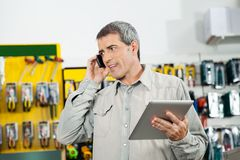 Man Holding Digital Tablet While Using Mobilephone. Mature man holding digital tablet while using mobilephone in hardware store Stock Image
