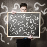Man holding direction sign with arrow questions Royalty Free Stock Images