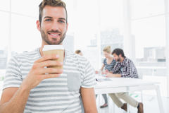 Man holding disposable coffee cup with colleagues in background Stock Photos