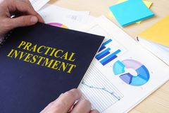 Man holding document with Practical investment. Man holding document with title Practical investment Stock Image