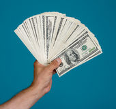 Man holding dollar bills. On a blue background Royalty Free Stock Photos